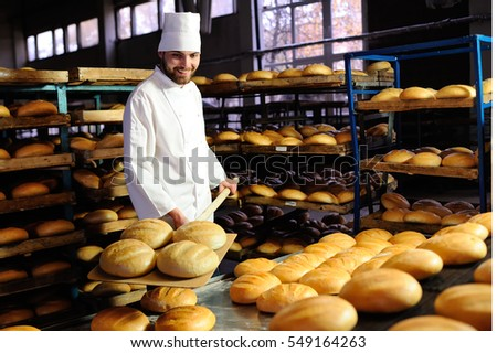 young handsome guy baker pulls out of the oven fresh bread at the bakery background #549164263