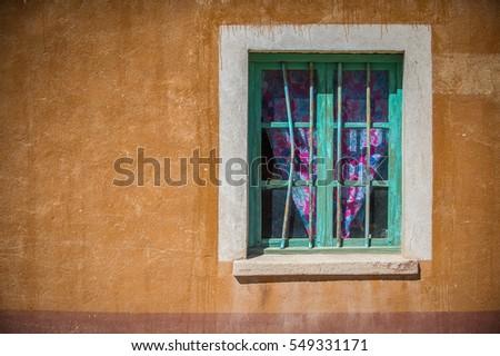 Green wood window on orange old wall #549331171