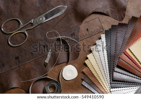 Crafting tools on natural cow leather in the tailoring workshop. Top view. Royalty-Free Stock Photo #549410590
