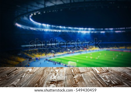 Wooden table against football stadium background Royalty-Free Stock Photo #549430459
