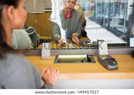 people, withdrawal, saving and finance concept - clerk with cash money and customer at bank office or currency exchanger #549457027