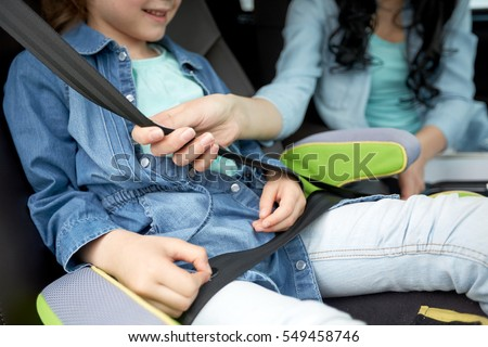 family, transport, road trip and people concept - happy woman fastening child with safety seat belt in car #549458746