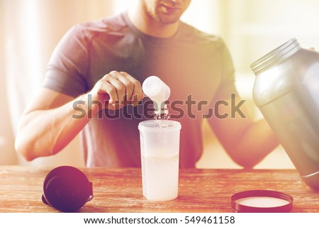 sport, fitness, healthy lifestyle and people concept - close up of man with jar and bottle preparing protein shake #549461158