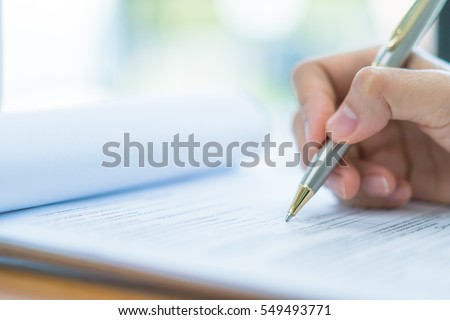 Hand with pen over application form Royalty-Free Stock Photo #549493771