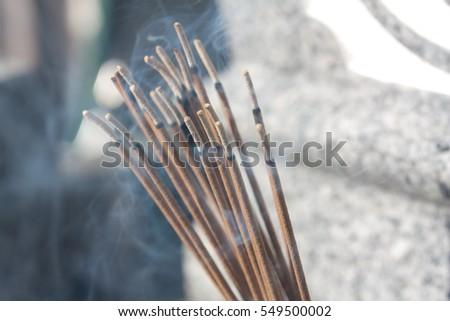 Incense stick smoke praying at the cemetery #549500002