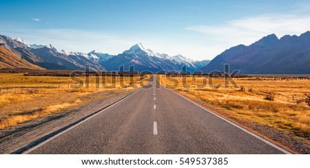 A long straight road leading towards a snow capped mountain in New Zealand Royalty-Free Stock Photo #549537385