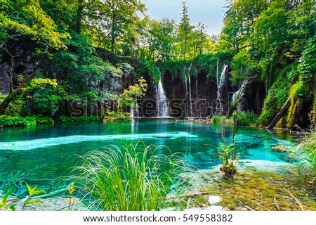 Waterfall over the turquoise waters of the lake. #549558382