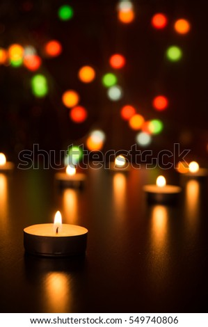 Concept One candle flame light at night with bokeh on dark background. Candles with light in a romantic decoration and defocused lights. Greeting card. Christmas background