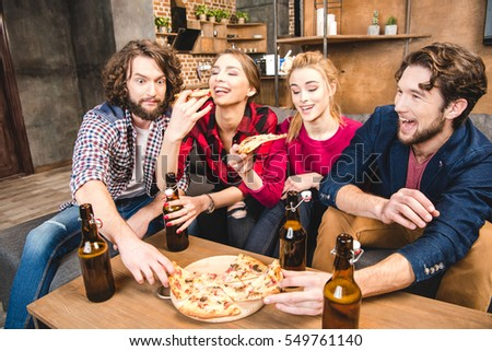 Smiling friends drinking beer and eating pizza while sitting on sofa  #549761140