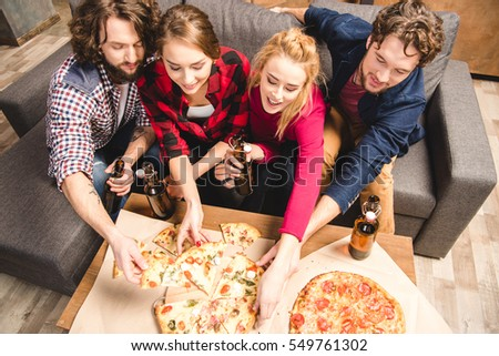 Happy friends enjoying pizza at home party  #549761302