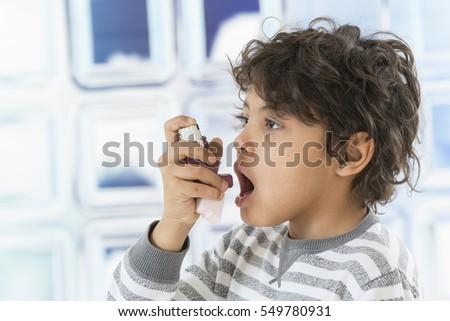 Boy using  nasal spray bottle.- allergy concept Royalty-Free Stock Photo #549780931