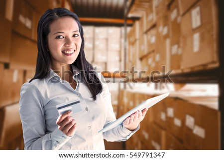 Smiling businesswoman holding laptop and credit card against shelves with boxes in warehouse #549791347