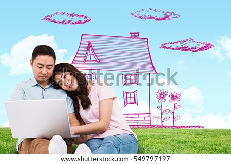 Couple working on laptop against blue sky over green field #549797197