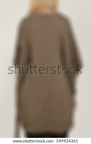 Womens fashion clothing theme creative abstract blur background with bokeh effect. Young woman demonstrates designer clothing piece in studio environment for internet store #549924361