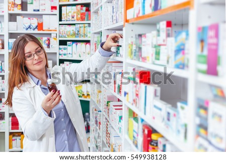 Woman pharmacist holding prescription checking medicine in pharmacy (or drugstore Royalty-Free Stock Photo #549938128
