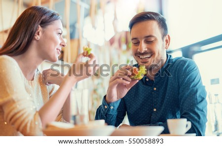 Happy loving couple enjoying breakfast in cafe. Love, food, lifestyle concept. #550058893