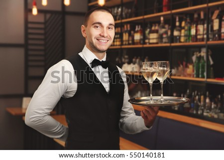 Young handsome waiter holding tray with wine glasses in the restaurant #550140181