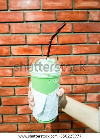 Ice Green tea glass in hand. #550223977