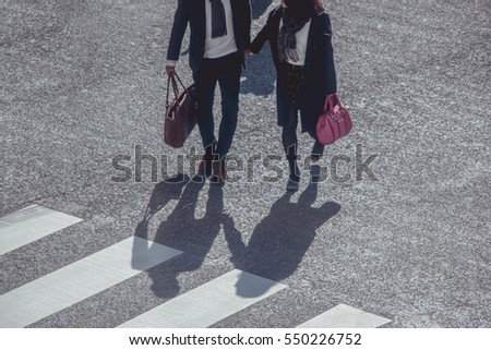 Silhouette of a couple hold hand across Pedestrians at Shibuya Junction, Tokyo, Japan #550226752