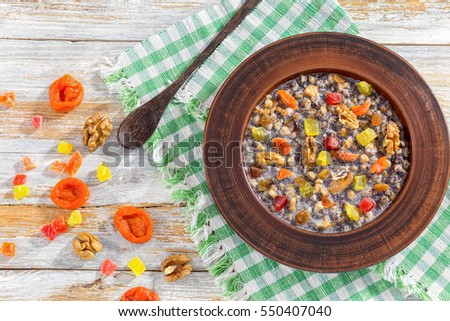 Sweet wheat kutia with nuts, poppy seeds, dried fruits. succade and honey in clay bowl with spoon on kitchen cloth on wooden planks. with ingredients on background, view from above #550407040