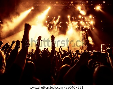 silhouettes of concert crowd in front of bright stage lights #550407331