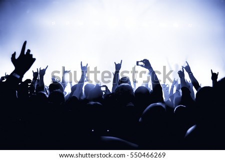silhouettes of concert crowd in front of bright stage lights #550466269