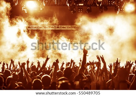 silhouettes of concert crowd in front of bright stage lights Royalty-Free Stock Photo #550489705