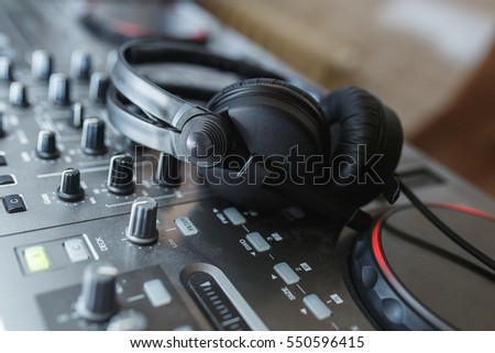 DJ Mixer with headphones. Elements and details of artists working tools - DJ console with knobs and black headphones. Soft focus. #550596415