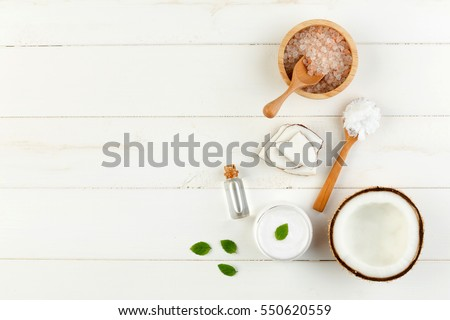 Homemade coconut products on white wooden table background. Oil, scrub, milk, lotion, mint and himalayan salt from top view. Good for space and background #550620559