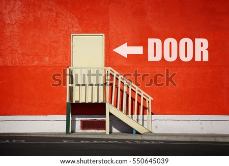 funny  sign and arrow pointing to door against orange wall