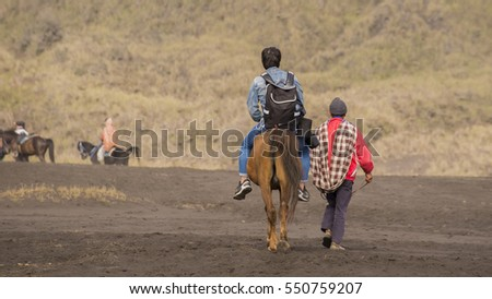 Riding with horse to see crater of Mount Bromo Volcano, East Java, Indonesia #550759207