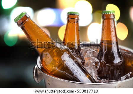 cold bottles of beer in bucket with ice in a restaurant setting Royalty-Free Stock Photo #550817713