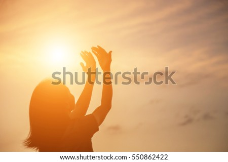 Silhouette of woman praying over beautiful sky background #550862422
