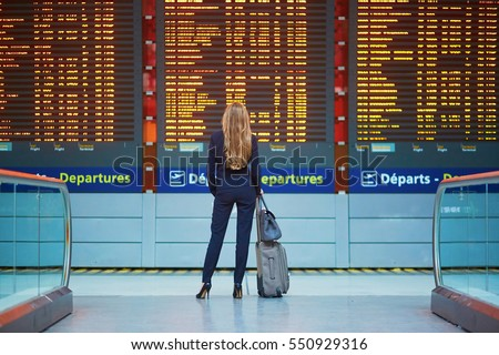 Young elegant business woman with hand luggage in international airport terminal, looking at information board, checking her flight. Cabin crew member with suitcase. Royalty-Free Stock Photo #550929316