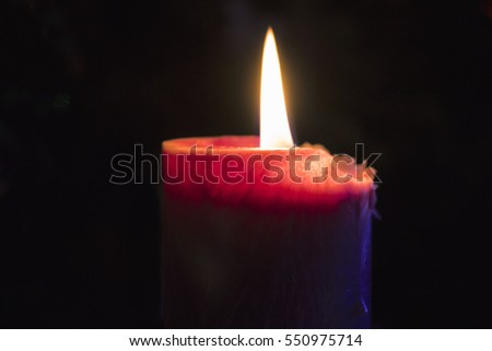 Burning red candle in the night #550975714