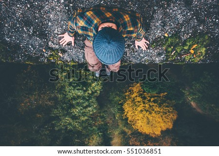 Man Traveler sitting on cliff bridge edge with forest aerial view Travel Lifestyle adventure vacations concept  Royalty-Free Stock Photo #551036851