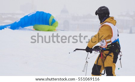 Snowkiting in the snow on frozen river, kite surfer ready for sliding #551069116