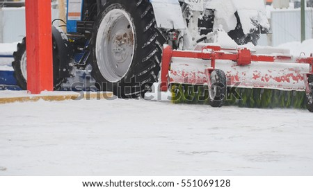 Tractor plowing snow on street, close up #551069128