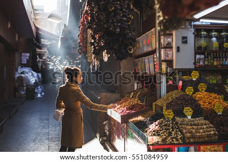 Woman chooses in the market nuts and dried fruit, the buyer tries goods at Grand Bazaar Istanbul #551084959