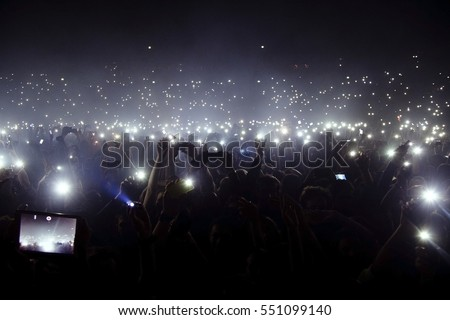 Group of people holding cigarette lighters and mobile phones at a concert  #551099140
