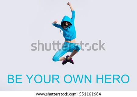 """One beautiful young fit modern dancer lady in blue sportswear hoodie sweater working out, dancing and jumping, full length. Photo with motivational text """"Be your own hero"""""""
