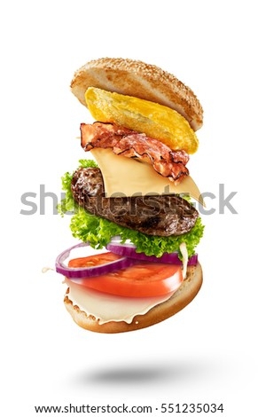 Maxi hamburger with flying ingredients isolated on white background. High resolution image #551235034