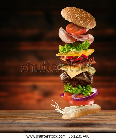 Maxi hamburger with flying ingredients placed on wooden planks. Copy space for text, high resolution image