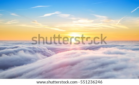 Beautiful sunset above clouds from airplane perspective. High resolution image Royalty-Free Stock Photo #551236246