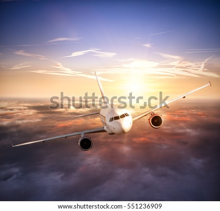 Commercial airplane flying above clouds in dramatic sunset light. Very high resolution of image #551236909
