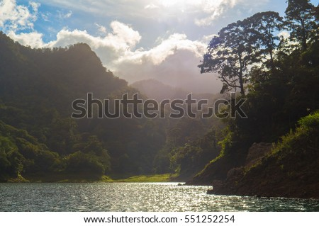 Natural Landscape with lake and trees. Experimental light wild lake view. Mountain lake panorama in sunlight. Relaxing nature wallpaper or banner template. Summer weekend travel to forest camp