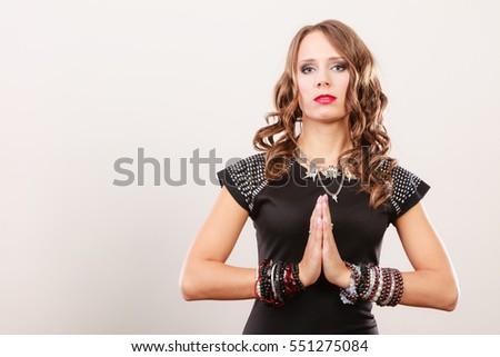 Pretty young woman wearing multiple bracelets jewellery necklace in black elegant evening dress #551275084