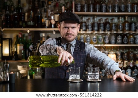 Bartender bartender is pouring a drink and looking at the camera #551314222