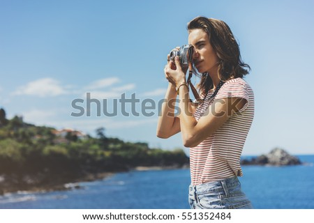 Tourist traveler photographer making pictures seascape on vintage photo camera on background yacht and boat piar, hipster girl enjoying peak nature holiday, mockup ocean waves view, blurred backdrop