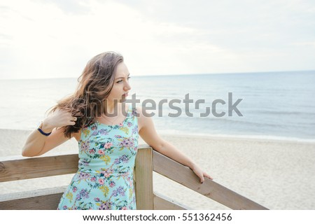 Brunette girl sitting on the wooden stairs in park and smiling #551362456